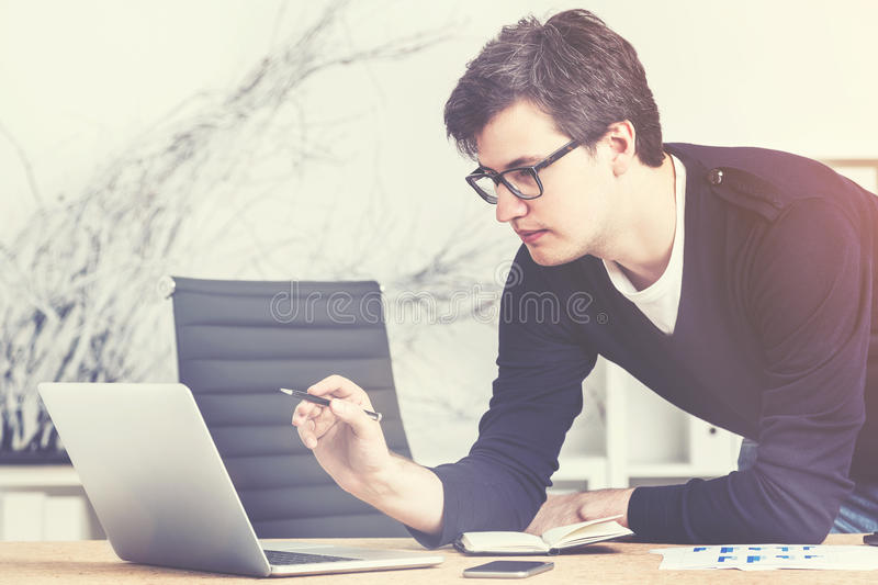 Young enterpreneur in glasses and sweater working, toned royalty free stock photography
