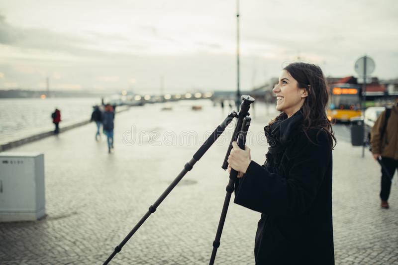 Young enthusiastic female photographer setting up lightweight carbon travel tripod for sunset/sunrise log exposure still shot royalty free stock images