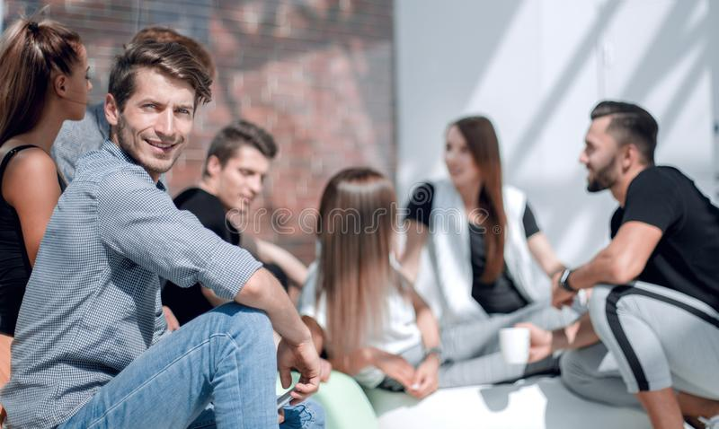 Young entrepreneur on the background of a group of young designers. Photo with copy space stock image
