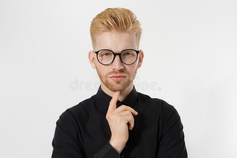 Young entrepreneur Generate Business Ideas. Close up of thinking Man in black shirt and glasses isolated, copy space. Self. Improvement, serious male face stock photo