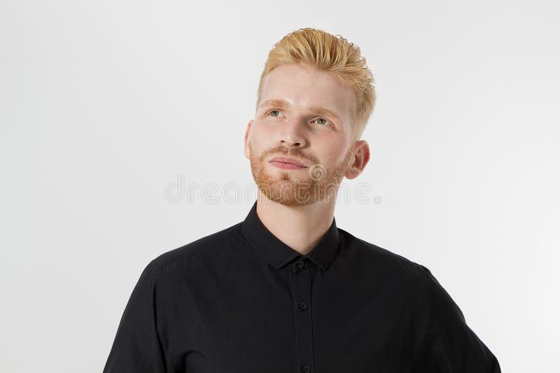 Young entrepreneur Generate Business Ideas. Close up of thinking Man in black shirt isolated with copy space. Self improvement. And serious male face. Redheaded stock photo