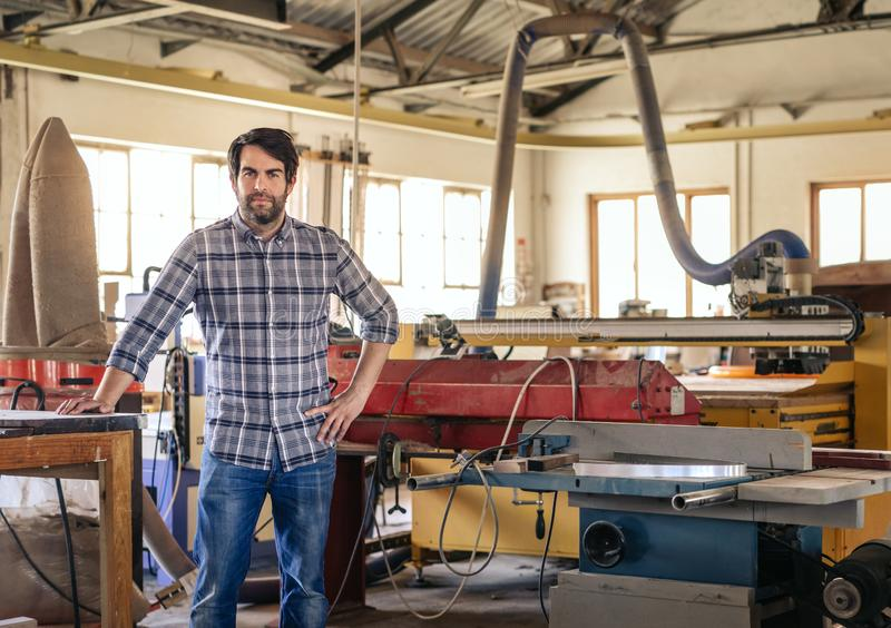 Young entrepreneur leaning on a table in his large workshop royalty free stock image