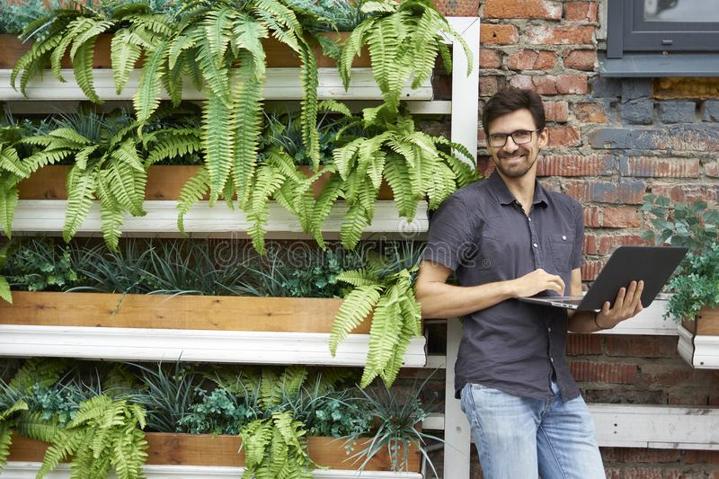 Young entrepreneur smiling working using modern laptop. Standing near brick wall, plants, eco office. Successful business people royalty free stock photo