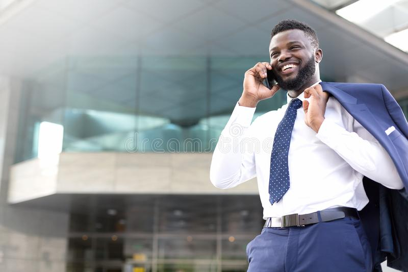 Young entrepreneur standing outside the office and talking on the mobile phone. Copy space royalty free stock images