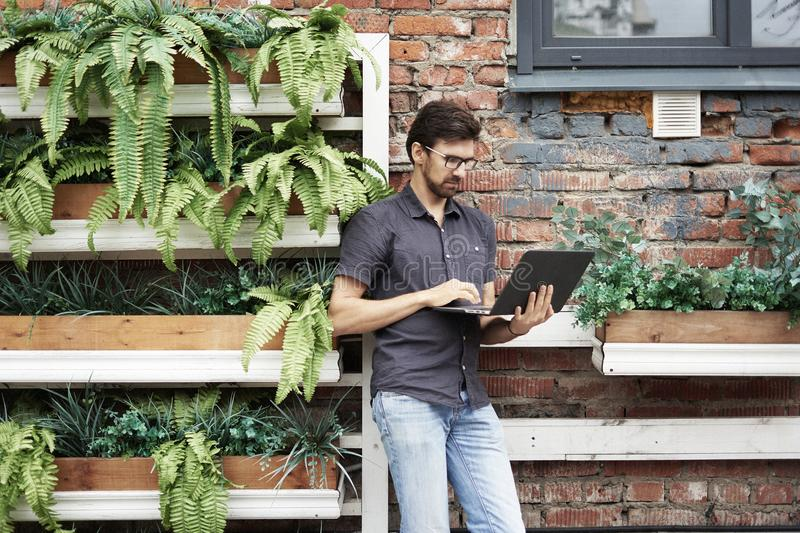 Young entrepreneur working outside using modern laptop. Standing near brick wall, plants, eco office. Successful business people royalty free stock image