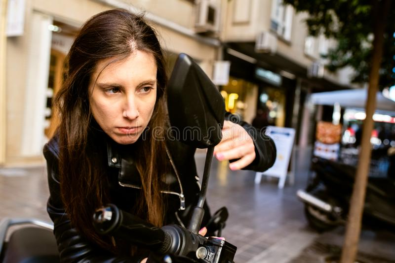 Young entrepreneur worried about her appearance just before an important meeting, touching up makeup on the street stock images