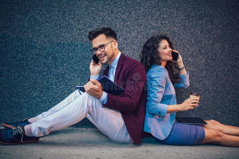 Entrepreneurs sitting down in front of a modern office building and using phone. Brainstorming outside in a beautiful day. Young entrepreneurs sitting down in royalty free stock images