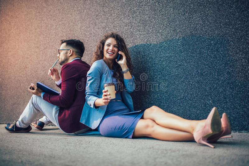 Entrepreneurs sitting down in front of a modern office building and using phone. Brainstorming outside in a beautiful day. Young entrepreneurs sitting down in stock images