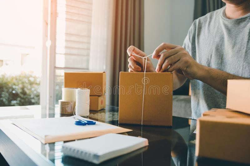 Young entrepreneurs are tie a rope cardboard boxes to pack the products for customers at home office stock photos