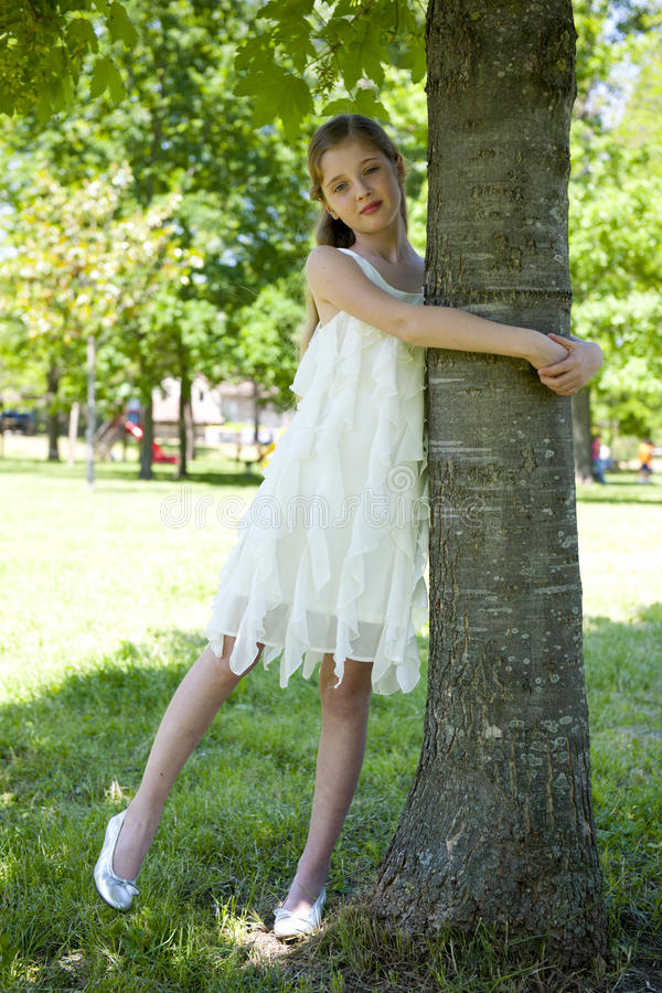 Young environmentalist. Blonde little girl embracing a tree stock photography