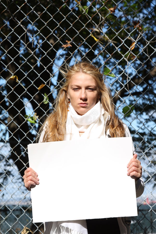 Young environmentalist girl. Young female environmentalist expressing eco-minded ideas. She is holding a blank sign - just type in your own message royalty free stock photo