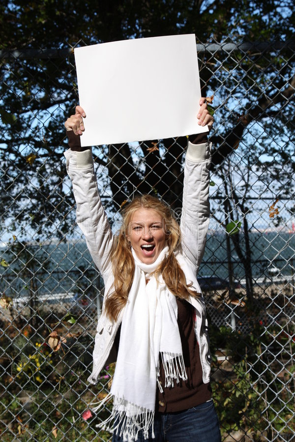 Young environmentalist girl. Young female environmentalist expressing eco-minded ideas. She is holding a blank sign - just type in your own message royalty free stock image