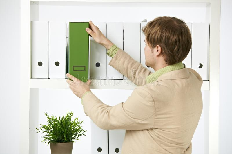 Young environmentalist with green folder. Young environmentalist in office holding green folder royalty free stock photography