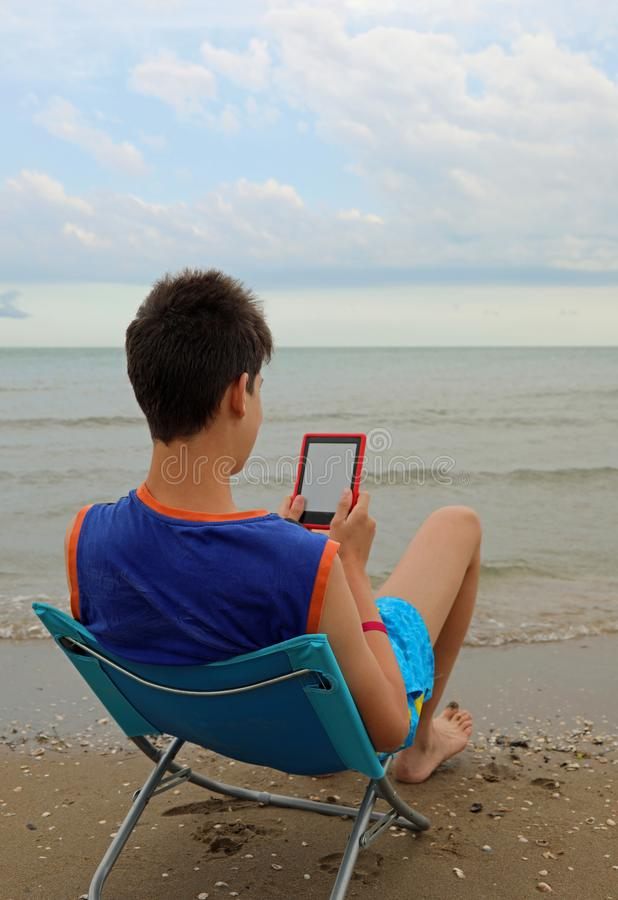 Young ereader reads an ebook. On the beach royalty free stock photos