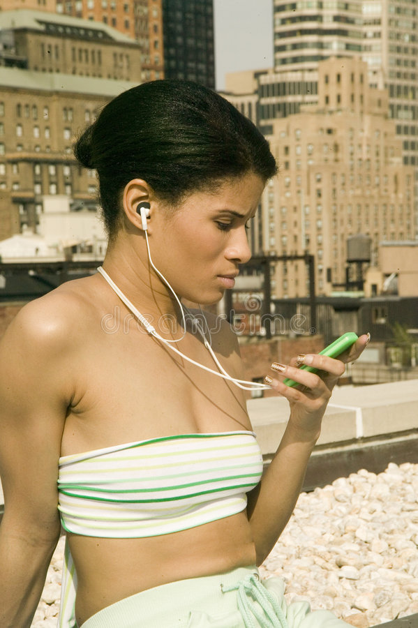 Young ethinc girl listens to music royalty free stock photography