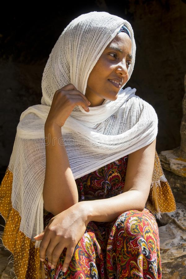 Abuna Yemata Guh, Tigray rock hewn churches. Gheralta massif. Young Ethiopian woman sitting at the entrance of the Abuna Yemata Guh rock hewn church in Tigray stock photography