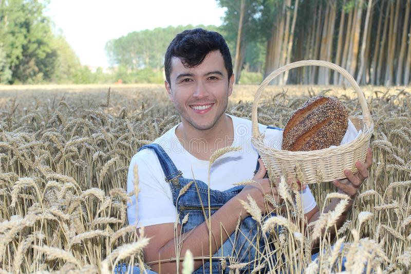 Young ethnic farmer holding bread in natural environment royalty free stock photography