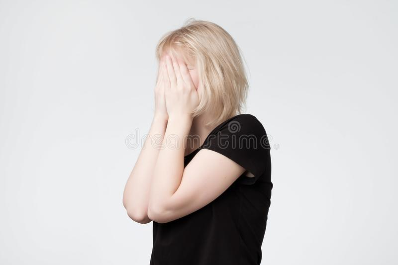 Young european blonde woman in black t-shirtr hides her face. Studio photo isolated on gray background. She has social phobia, trying to be anonym royalty free stock image