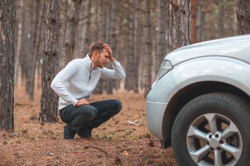 A young guy, sitting near a gray broken car and holding behind head. In the autumn forest. stock image