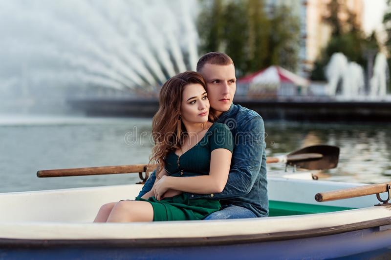 Young european couple is boating on a lake, young man and his girlfriend are sitting into boat at sunset, couple in love royalty free stock photo