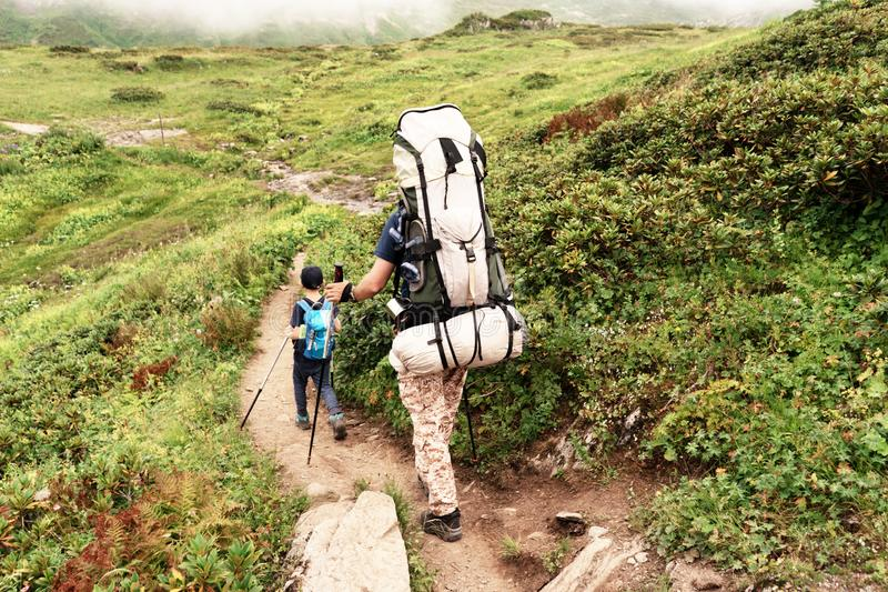A young European family of tourists, a father with heavy backpack and a young son waiking on the mountain trails. stock images