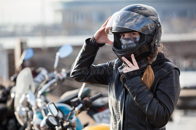 Young girl biker trying black motorcycle helmet for ride on bike stock images