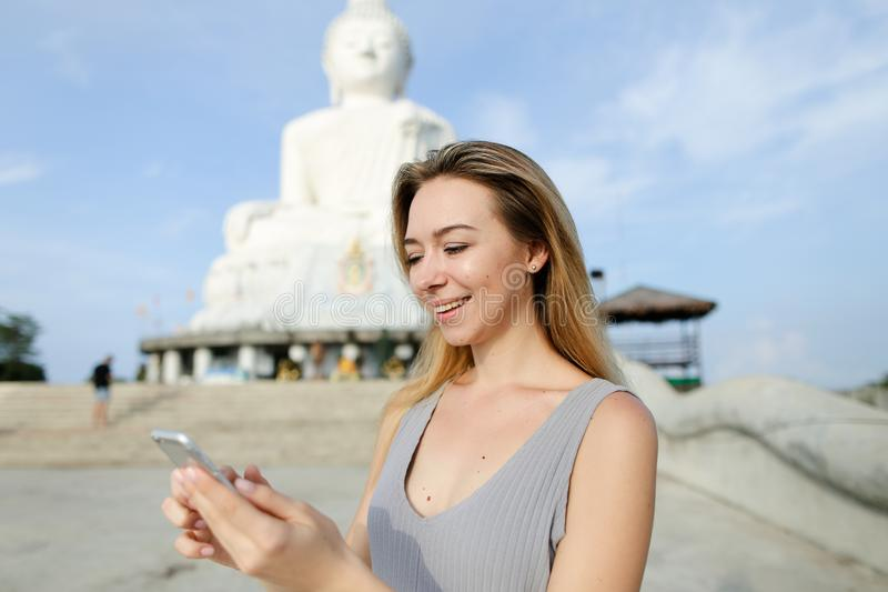Young european girl chatting by smartphone near Buddha white statue in Phuket. royalty free stock photography