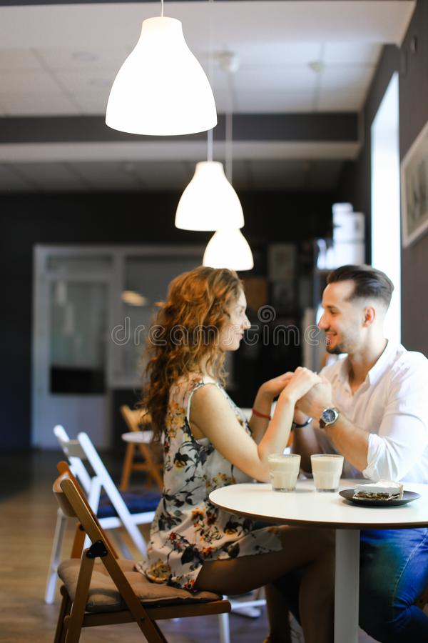 Young european girl sitting with boyfriend at cafe and resting. stock image