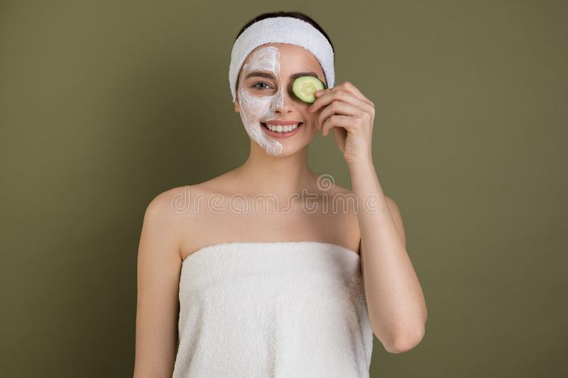 Young european girl with white cosmetic masak on her face. Holding a slice of cucumber over her eye and smiling  on green background royalty free stock image