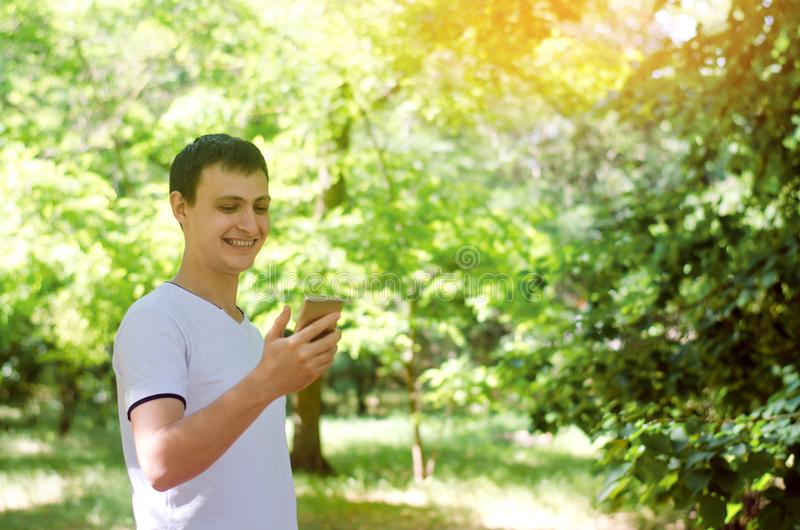 Young european guy looking into smartphone and smiling. telephone dependence, social networks. work on the Internet. write message stock images