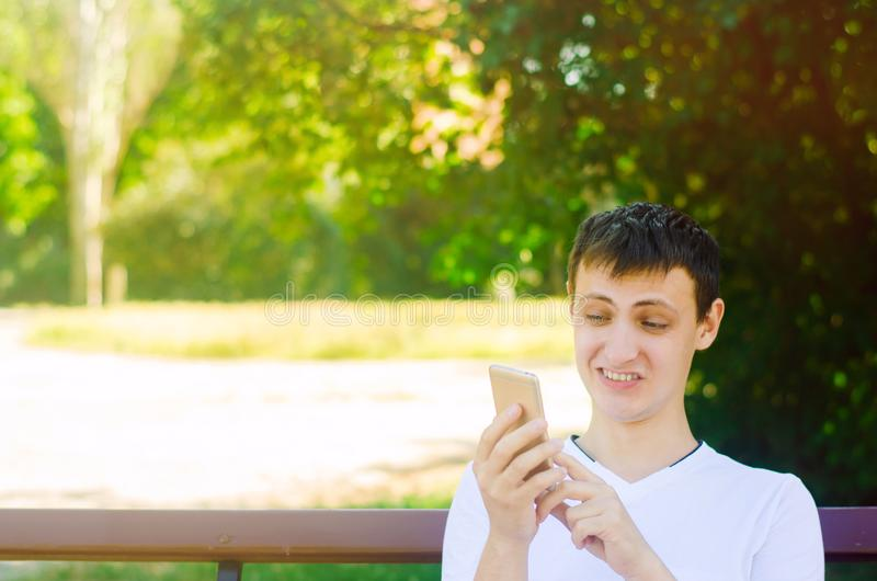 A young european guy sits on a bench in a city park and makes a. Funny face looking into the phone. The concept of extreme surprise and disgust, suddenness stock photo