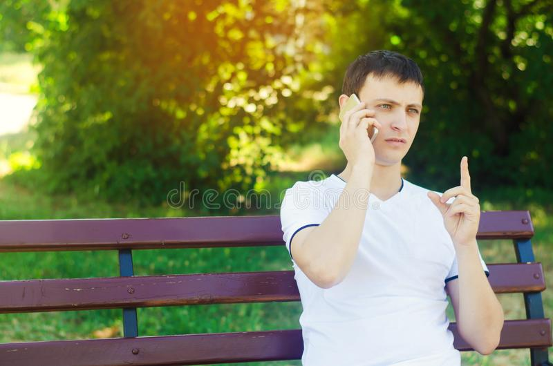 A young European guy in a white T-shirt speaks on the phone and sits on a bench in the city park and points with your finger. The. Concept of solving problems stock photo