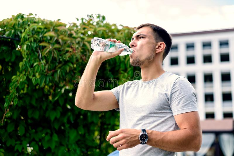 Young European man drinking water from plastic bottle on background of green bushes of trees on bright Sunny day royalty free stock image