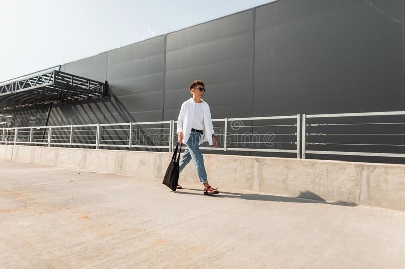 Young European man fashion model in trendy jeans in a stylish shirt in fashionable sandals in sunglasses with bag walks stock images