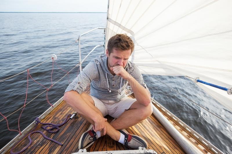 Young european man having a nausea seasickness. He is trying to stop vomiting. Travelling on old boat with sail royalty free stock images