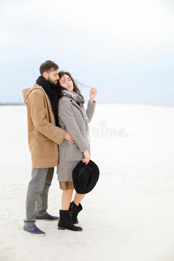Young european man hugging woman wearing grey coat and scarf in white winter background. Young european men hugging women wearing grey coat and scarf in white royalty free stock image