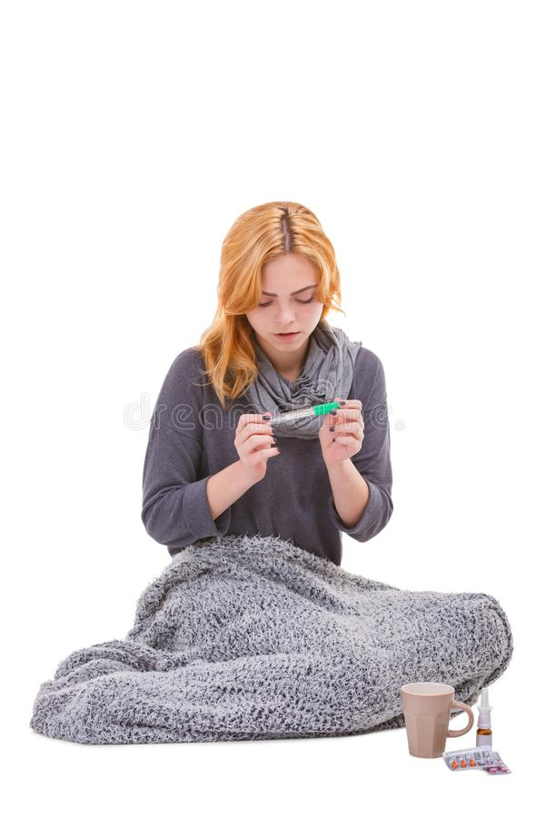 A sick girl, wrapped in a blanket, sits next to the medicines and holds a thermometer. Isolated. royalty free stock photos