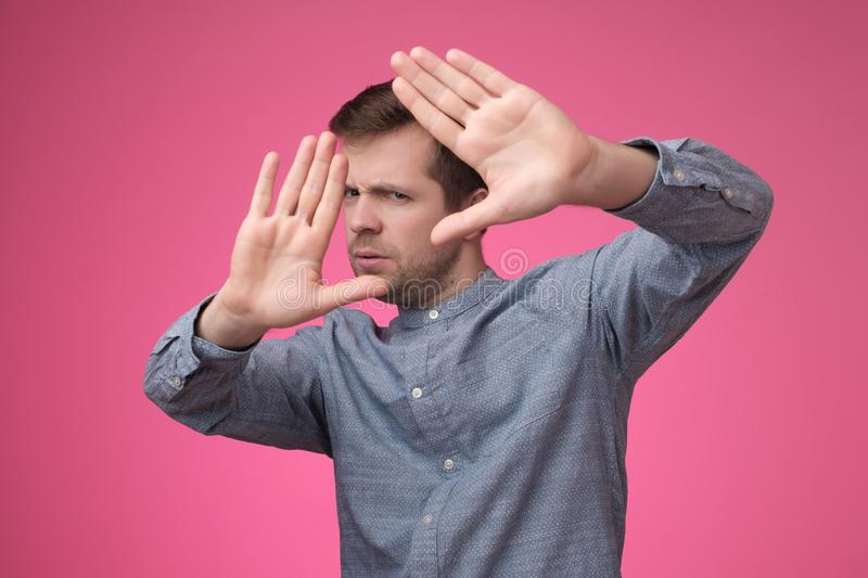 Young european shows refusal gesture. Leave me in piece, has angry expression royalty free stock image