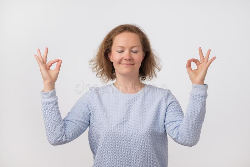 Young european smiling woman in pink sweater meditating, holding her hands in yoga gesture, feeling calm and positive stock images