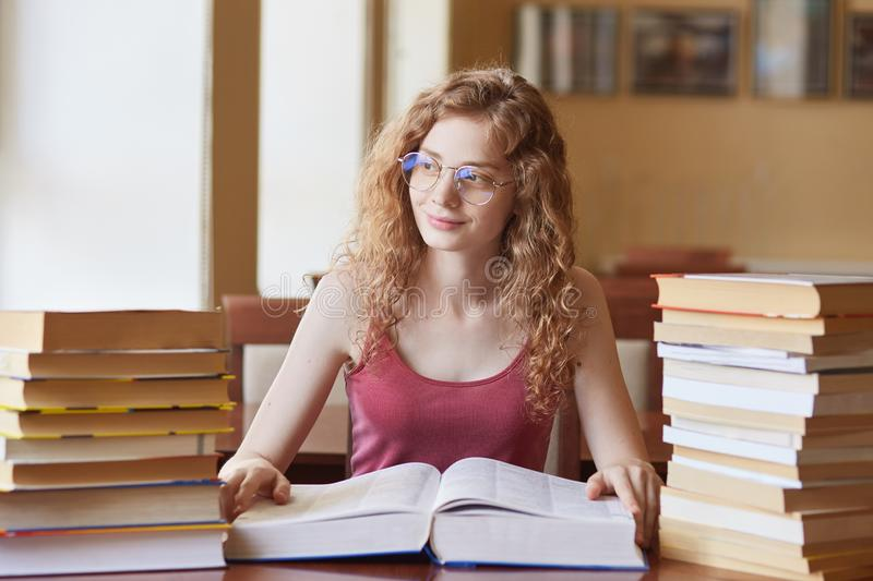 Young European sweet curly haired girl looking aside, sitting at desk. spending her time in library, having many books on desk, stock image