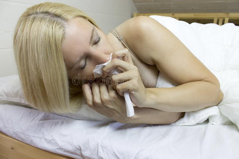 Young European upset and sick female with paper napkin blowing nose, lies on the pillow, closed eyes, indoor. Sinusitis treatment stock images