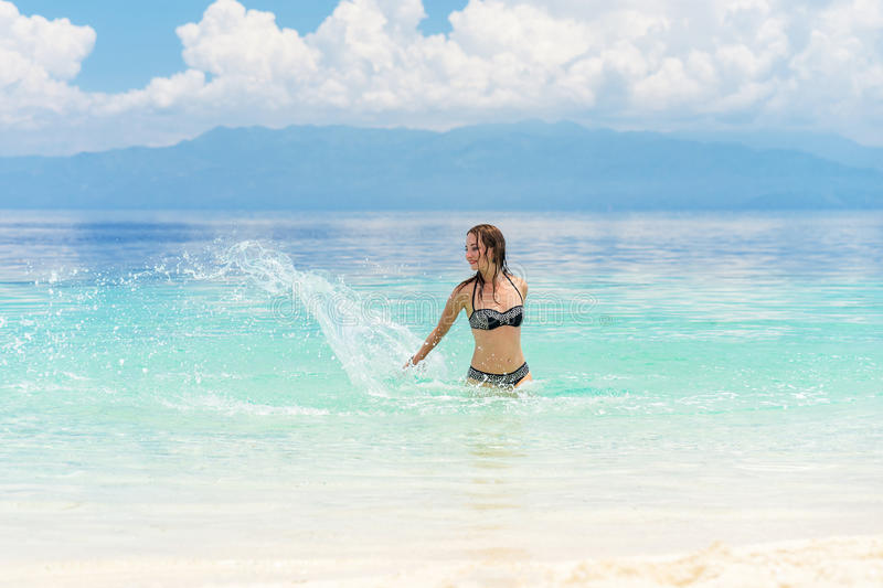 Young european woman in bikini with good mood splashing and dancing in beautiful tropical calm sea under cloudy soft sky. At sunny day stock photos
