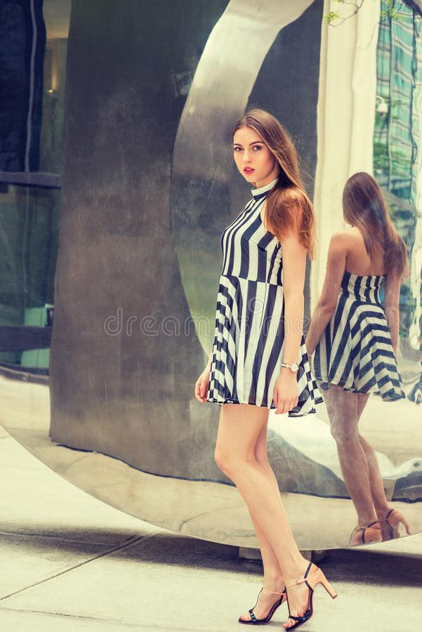 Young European Woman standing by mirror in New York City royalty free stock image