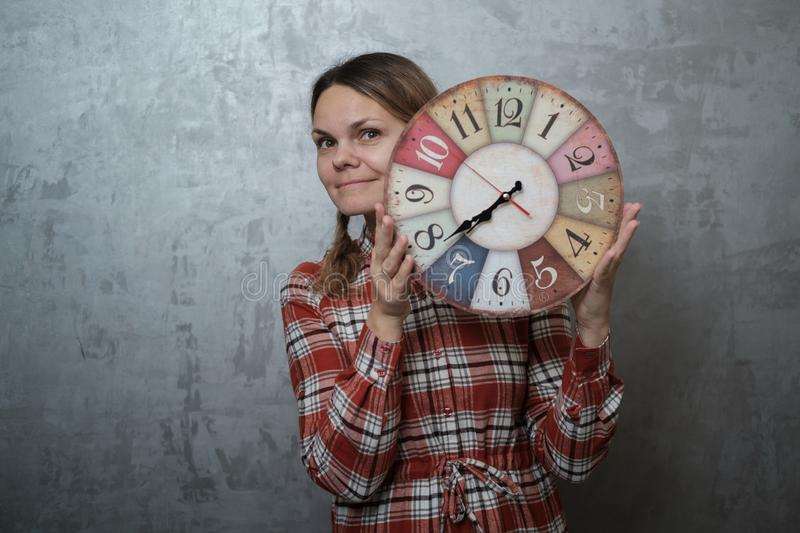 Young European woman in plaid dress holding round vintage watch royalty free stock image