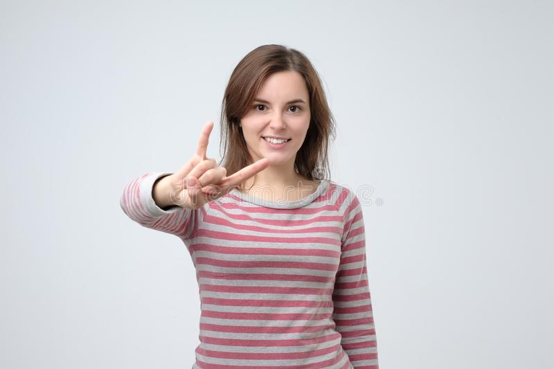 Young european woman showing rock and roll hand gesture posing in studio. royalty free stock photography
