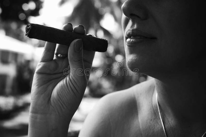 Young European woman smokes handmade cigar. Closeup monochrome photo with selective focus. Dominican Republic stock photo