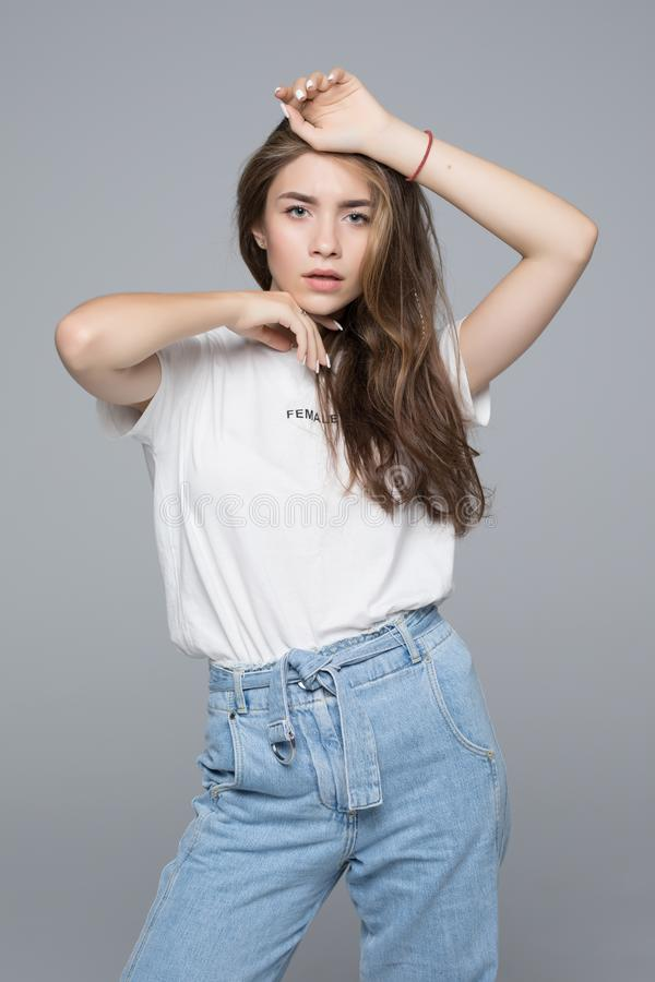 Young european woman wearing blank white tshirt with copy space for your logo or text, isolated on grey background stock photography