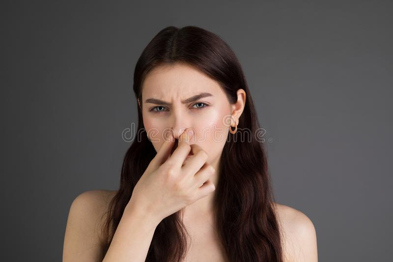 Young europian woman with brunette girl over isolated background smelling something stinky royalty free stock images