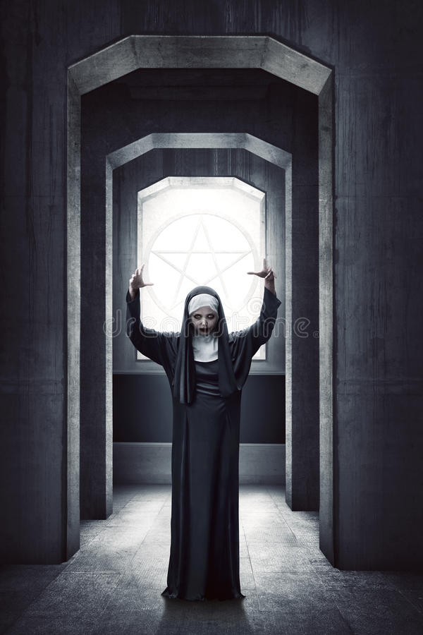 Young evil asian woman nun standing with white pentagram stock photo