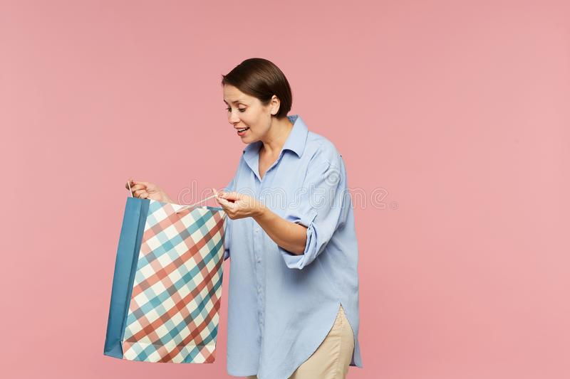 Young excited female in casualwear looking at surprise in open paperbag stock photography